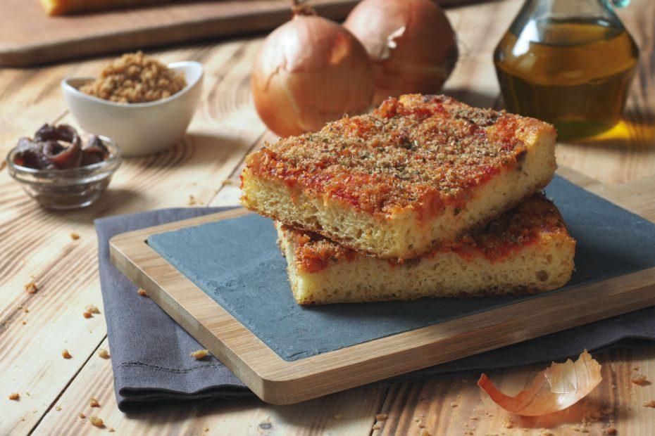 Pizza siciliana chamada sfincione, preparada com cebola, molho de tomate, anchovas, queijo caciocavallo e migalhas de pão